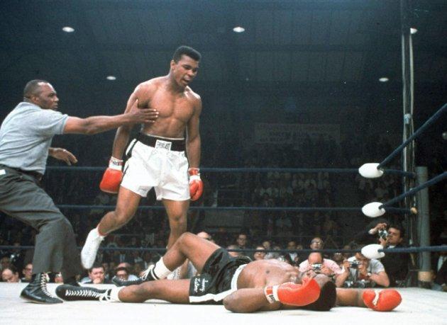 ARCHIVO - En esta imagen de archivo DEL 25 DE MAYO DE 1965, el campeón de peso completo Muhammad Ali es retenido por el árbitro Joe Walcott, a la izquierda, después de que Ali noqueara a su rival Sonny Listn en el primer asalto de su combate por el título en Lewiston, Maine. Ali, el indómito campeón peso completo cuyos demoledores golpes y avasalladora personalidad transformaron el deporte y le hicieron una superestrella mundial, ha fallecido, informó su familia. Tenía 74 años. (AP Foto/Archivo)